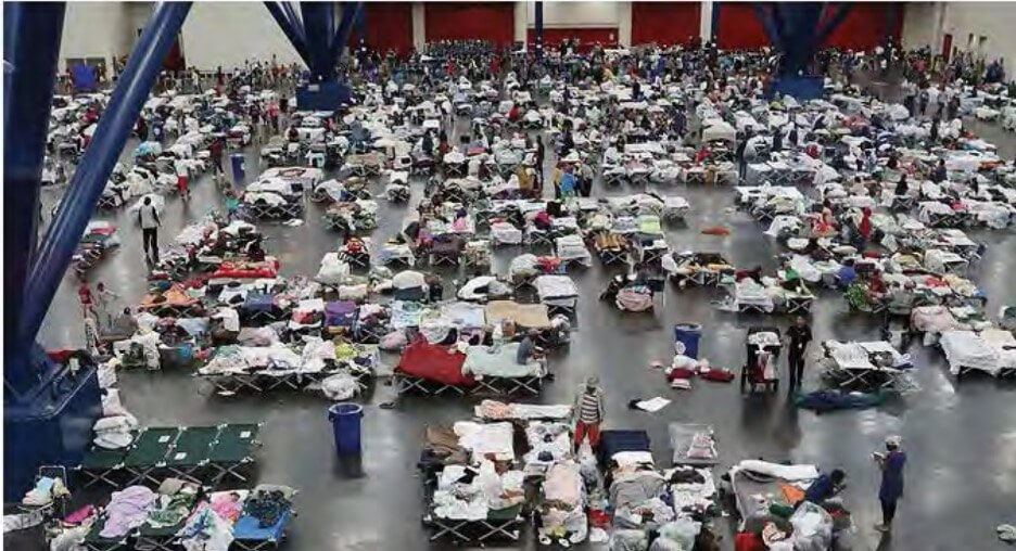 Large room filled with people on cots